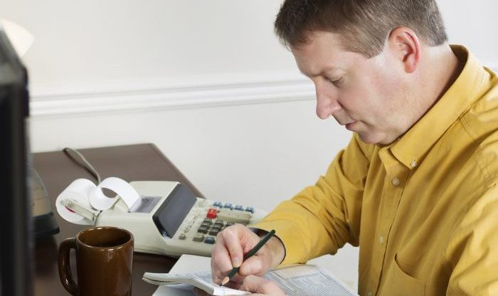 Photo of mature man, recording data from the computer, working on his taxes with tax booklet and pencil in hands