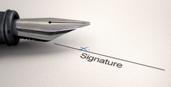 A white paper with a black line printed in ink showing the area for a signature to be signed and indicated with a hand written x with a fountain pen