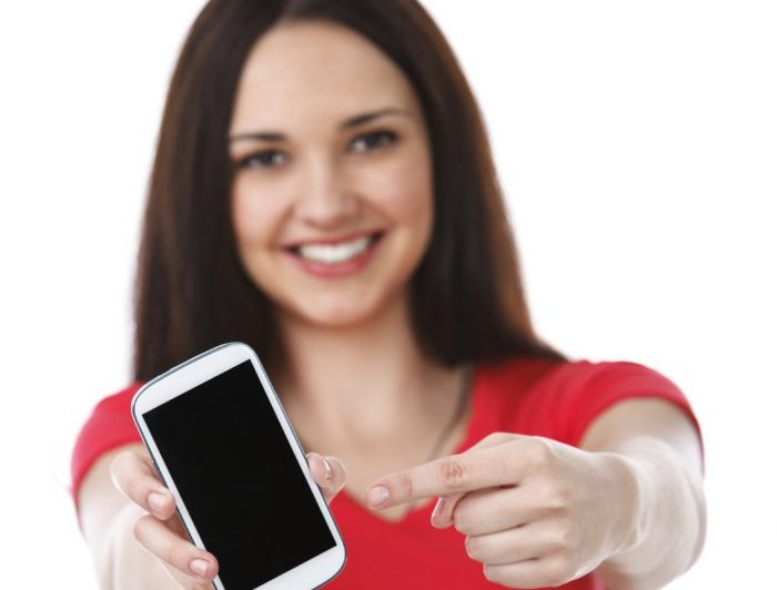 Young and beauiful woman showing smart phone. Isolated against white background.