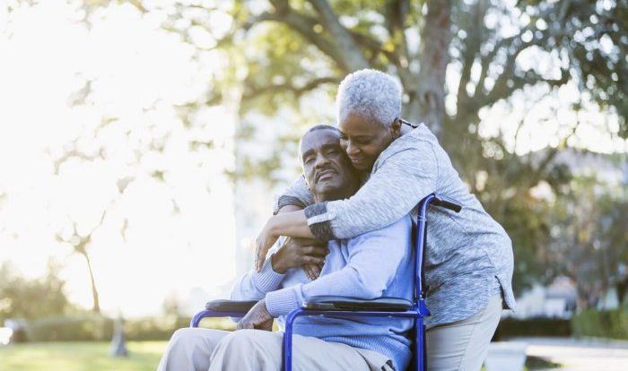 Portrait of a senior African American couple outdoors, showing their affection in the bright sunlight.  The man is sitting in a wheelchair, in the warm embrace of his devoted wife.  Their eyes are closed.