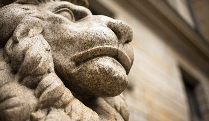 Granite statue of lion with building background. Short depth-of-field, focus on mouth.
