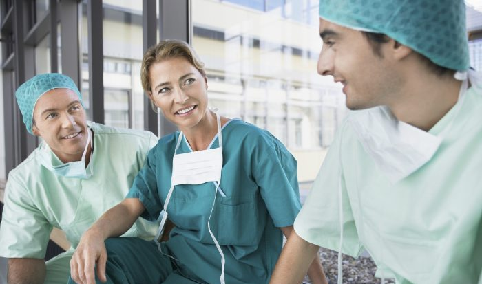 Female surgeon with male colleagues during break in the corridor