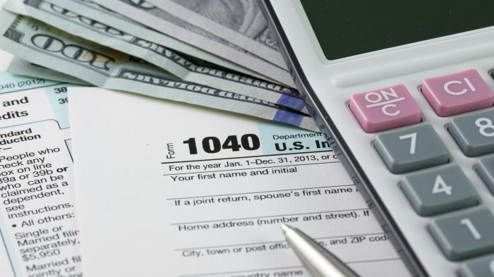 Filling out income tax forms with US dollar, calculator and pen