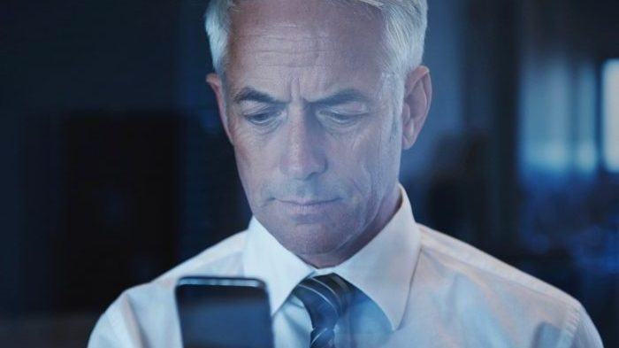 A mature businessman using his smartphone
